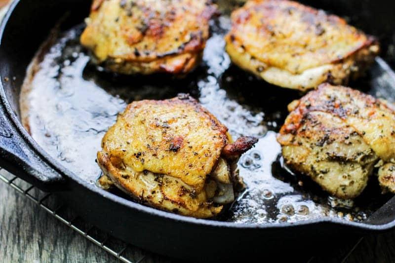 Keto Lemon Garlic Chicken Recipe Golden chicken in a cast iron pan.