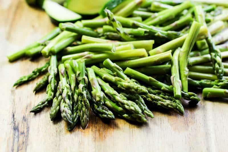 Keto Lemon Garlic Chicken Recipe asparagus ends on a wooden cutting board