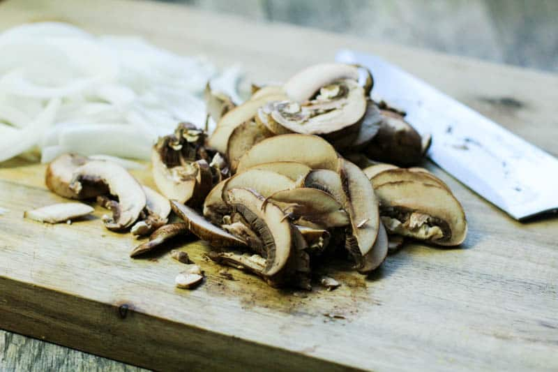 mushrooms and onions sliced on a cutting board
