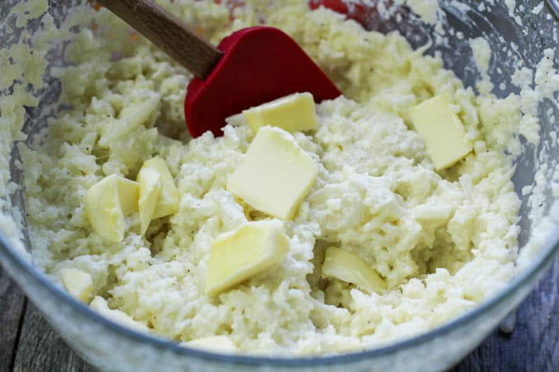 Mashed cauliflower with butter in a glass bowl.