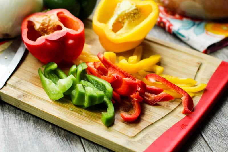 red yellow and green peppers on a cutting board