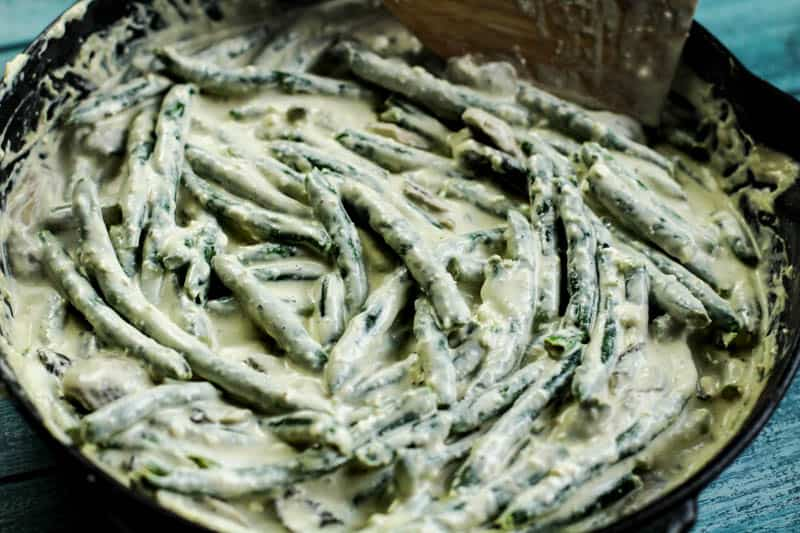 Green beans smothered in a creamy sauce in a pan.