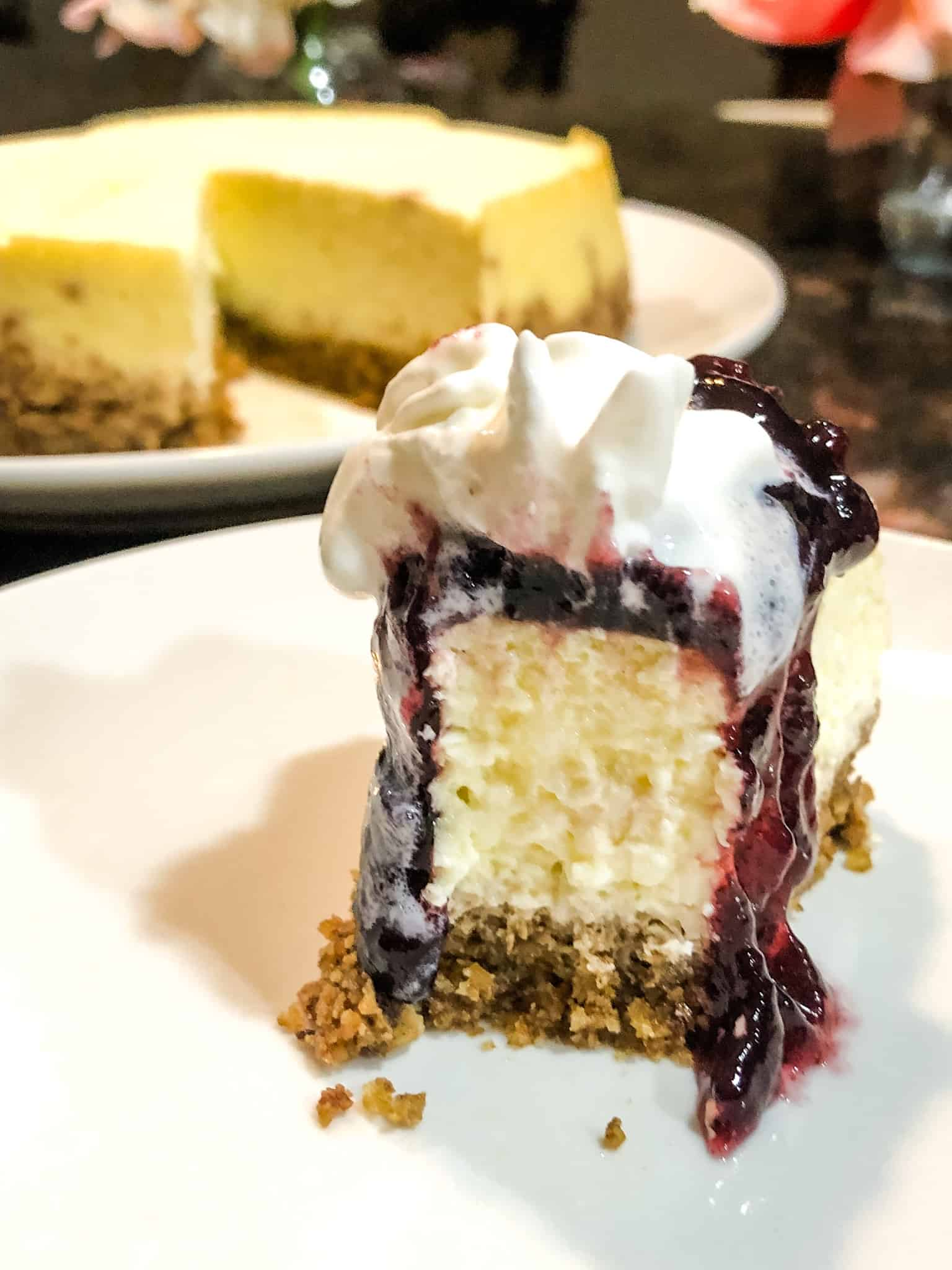 Keto Vanilla Cheesecake served with blueberry sauce and whipped cream
